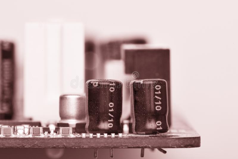 Electronic components are mounted on the device board Toned image. Electronic components are mounted on the device board Chips diodes capacitors chokes Toned royalty free stock photo