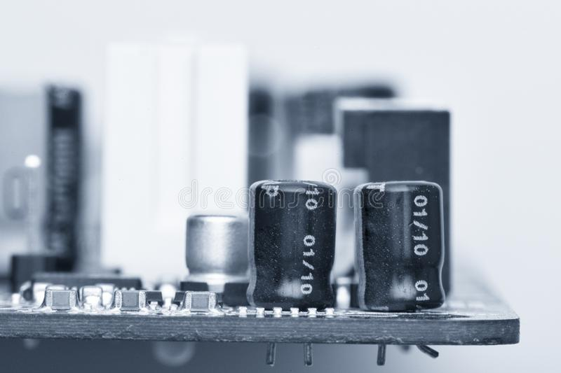 Electronic components are mounted on the device board Toned image. Electronic components are mounted on the device board Chips diodes capacitors chokes Toned stock photo
