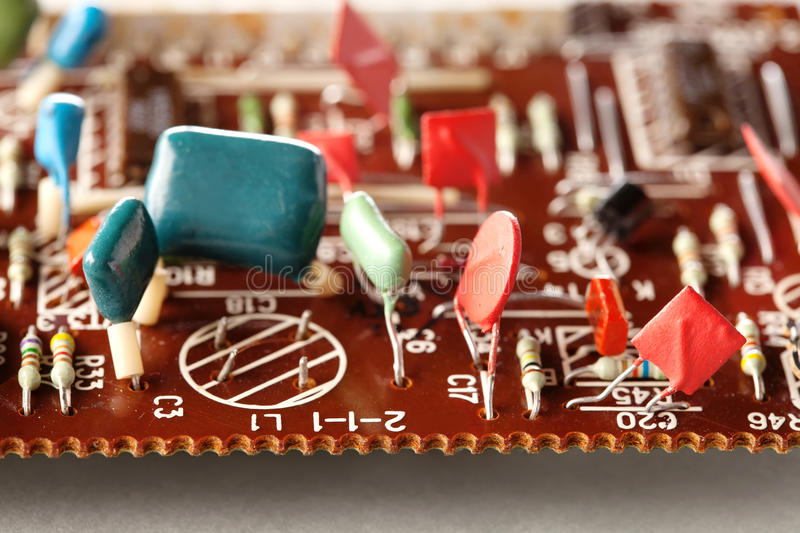 Electronic components vintage design. Selective focus Brown circuit board and soldering capacitors resistors macro view stock photography