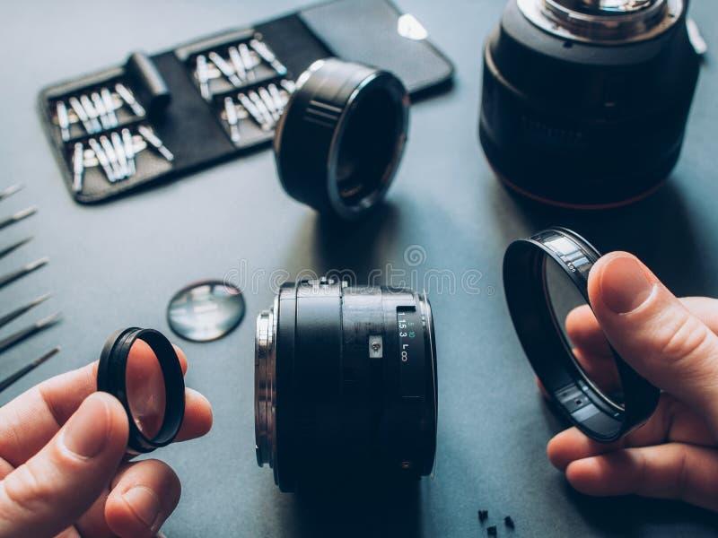 Electronic device maintenance photo camera lens. Electronic device maintenance. Top view of man hands repairing photo camera optical dslr lens royalty free stock photography