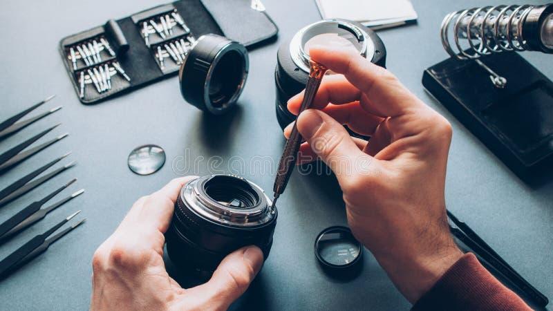 Electronic device service photo camera lens repair. Electronic device service. Top view of man hands repairing photo camera optical dslr lens royalty free stock photo