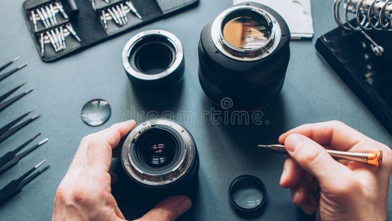 Electronic device service photo camera lens repair. Electronic device service. Top view of man hands repairing photo camera optical dslr lens stock image