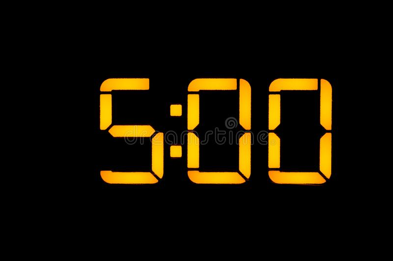 Electronic digital clock with yellow numbers on a black background shows the time of five zero zero in the morning. Isolate, close. Up stock photos