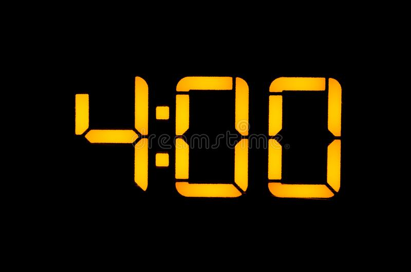 Electronic digital clock with yellow numbers on a black background shows the time four zero hours of the night. Isolate, close-up.  royalty free stock images