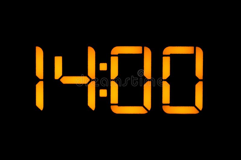 Electronic digital clock with yellow numbers on a black background shows the time Fourteen zero zero o`clock of the day. Close-up. Insulated stock photos