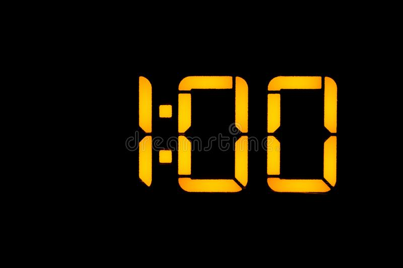 Electronic digital clock with yellow numbers on a black background shows the time one zero zero at night. Isolate, close-up.  royalty free stock image