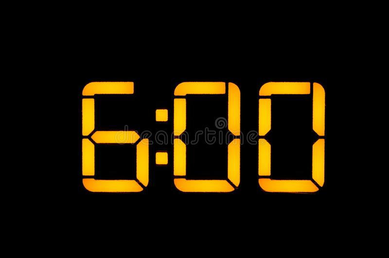Electronic digital clock with yellow numbers on a black background shows the time of six zero zero in the morning. Isolate, close-. Up royalty free stock image