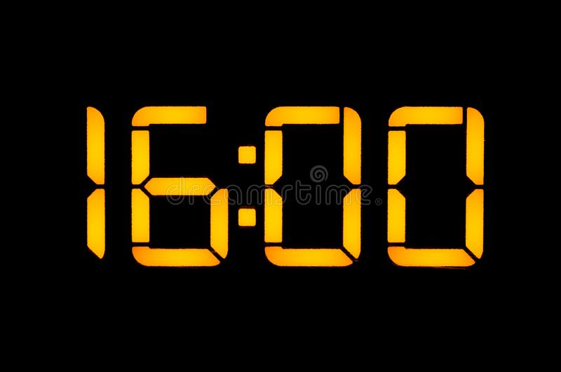 An electronic digital clock with yellow numbers on a black background shows the time. Sixteen zero zero o`clock of the day. Close. Up insulated stock photo