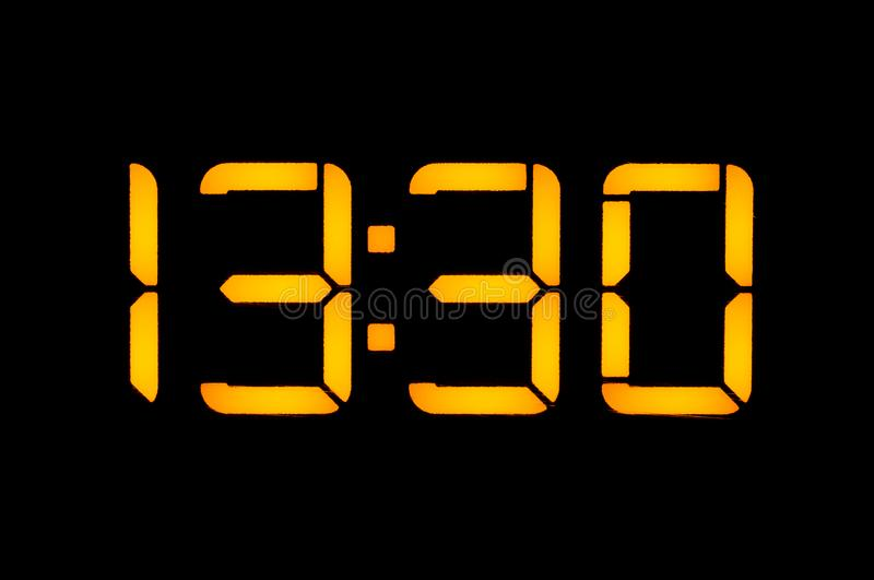 Electronic digital clock with yellow numbers on a black background shows the time Thirteen thirty hours of the day. Isolate, close. Up stock image