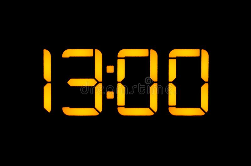 Electronic digital clock with yellow numbers on a black background shows the time Thirteen zero zero o`clock of the day. Isolate,. Close-up stock photos