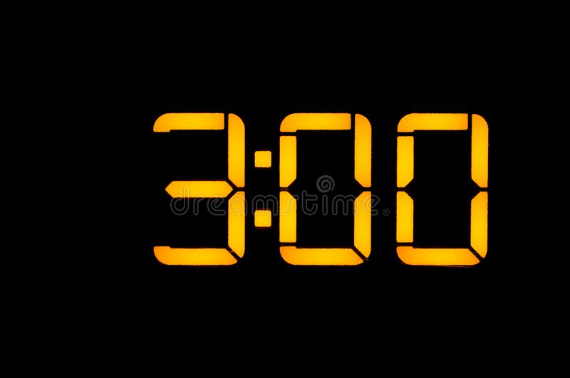 Electronic digital clock with yellow numbers on a black background shows the time three zero hours of the night. Isolate, close-up.  stock photography