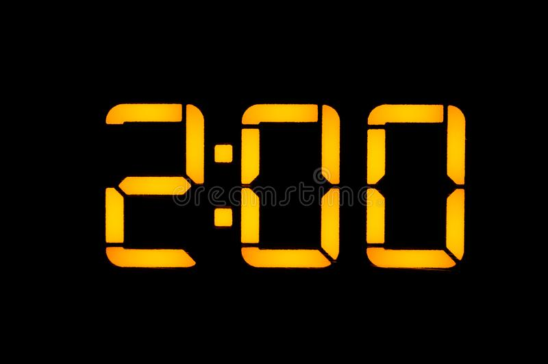 Electronic digital clock with yellow numbers on a black background shows the time two zero zero nights. Isolate, close-up.  royalty free stock photo