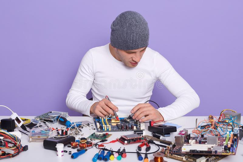 Electronic engineer measuring voltage of electronic curcuit board with help of multimeter, working alone in laboratory, having. Many electronic elements on royalty free stock photo