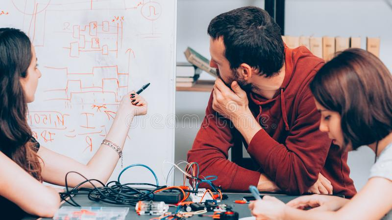 Electronic engineering brainstorming laboratory. Electronic engineering. Teamwork and brainstorming. Young technicians discussing wiring diagram at laboratory royalty free stock photo