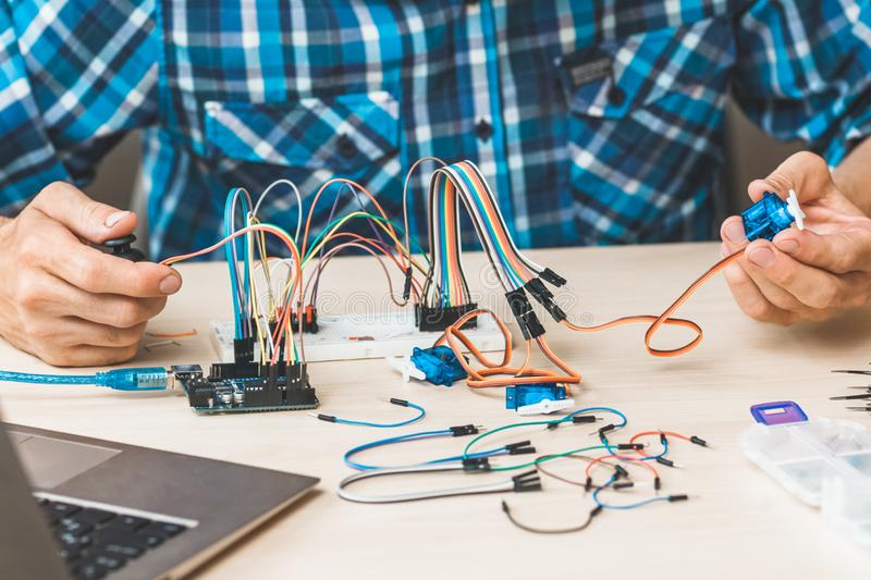 Electronic engineering scientific research lab. Electronic engineering scientific research. Cropped shot of programmer testing new device at lab royalty free stock photography