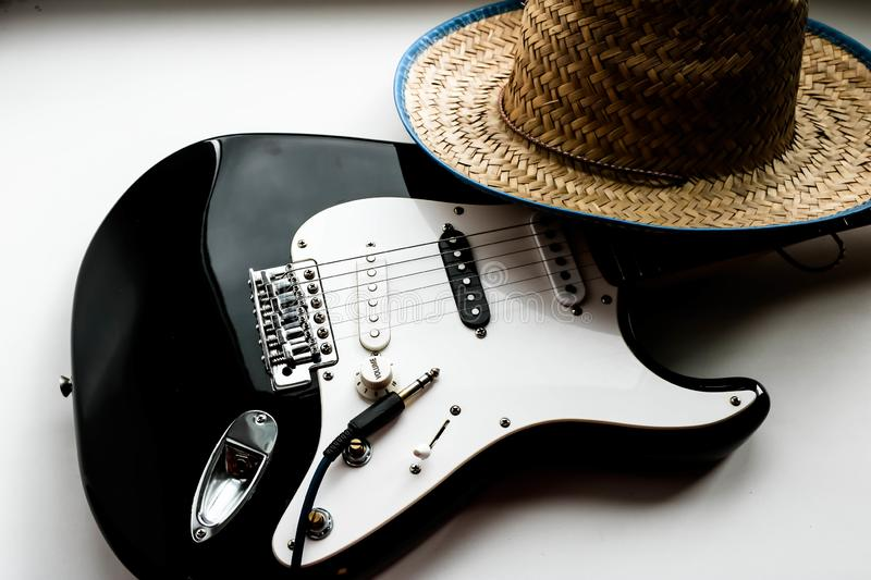 Electronic guitar and cowboy hat on the white background. Country music concept. American culture. Country music concept theme with a cowboy hat and electronic royalty free stock photography