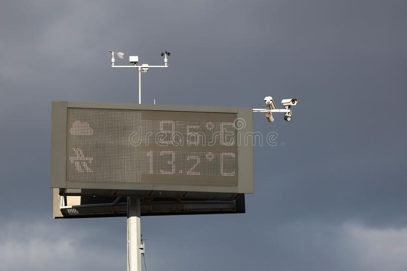 Electronic information board measuring temperature against the backdrop of thunderclouds. Security cameras and weather sensors. Infrastructure assistance to royalty free stock photography