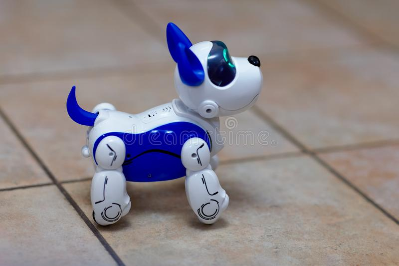 Electronic interactive toy dog puppy on a beige ceramic floor background of selective focus. High technology concept, pet of the f stock photos