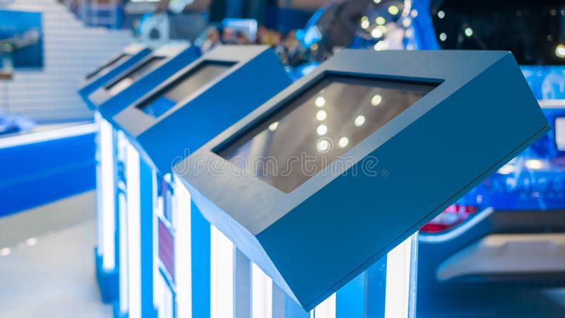 Electronic kiosks with touchscreen displays at modern trade show or exhibition. Electronic multimedia kiosks in row with touchscreen interactive displays at stock image