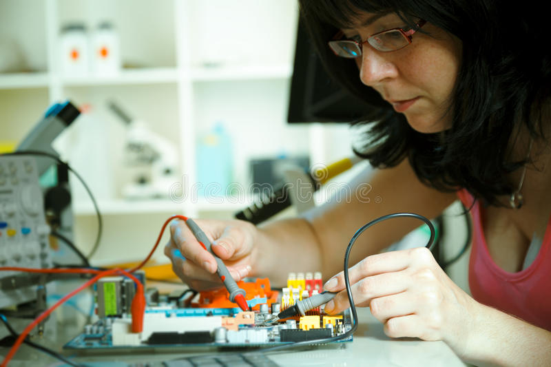 Electronic laboratory. Girl debugging an electronic precision device royalty free stock image