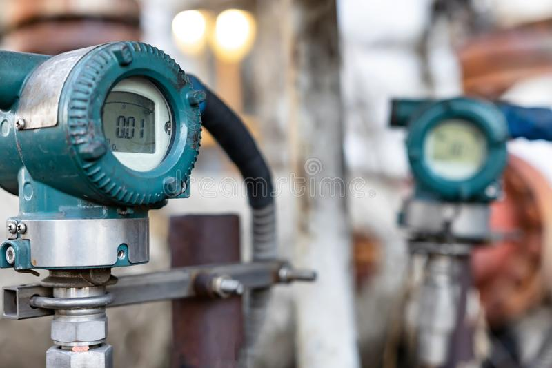 Electronic measuring device with display mounted on pipeline. At old chemical plant royalty free stock photo