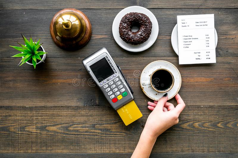 Electronic payments. Pay the bill by card concept. Bank card inserted in payment terminal near bill, service bell. Coffee and donut on dark wooden background royalty free stock photos