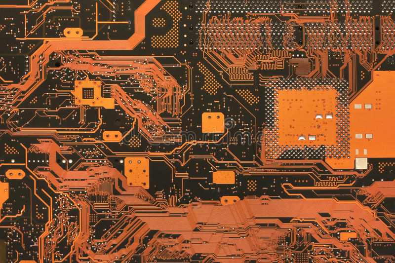 Electronic PCB back. Photo of the back of a motherboard showing the traces on the PCB forming interesting paths. Motherboard is indeed orange but it is easy to royalty free stock image