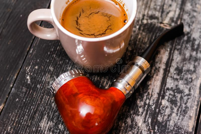 Electronic pipe and cup of coffee royalty free stock images