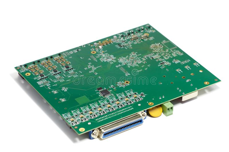 Electronic printed circuit board with chips and other components, green color, reverse side, angled view, isolated on white stock photo