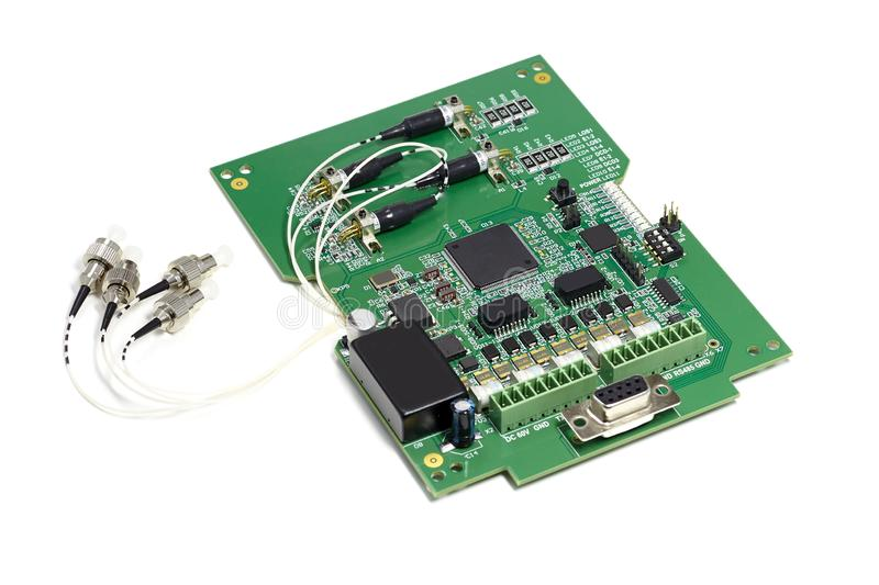 Electronic printed circuit board with microchip, many electrical components and optical connectors stock photography
