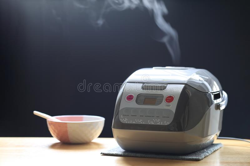 Electronic rice cooker in the kitchen on dark background stock image
