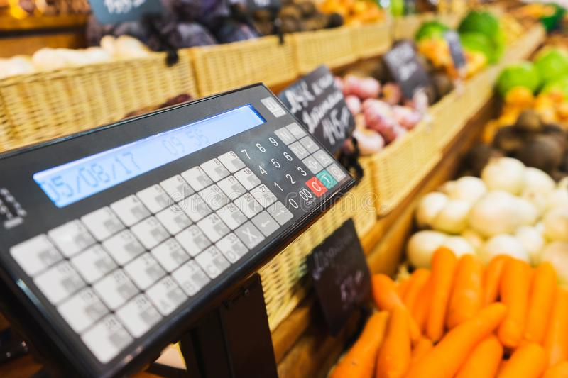 Electronic scales and control panel with a display on the counter of the vegetable market. Farm products and healthy food. Fruits and vegetables, trade. Soft royalty free stock photos