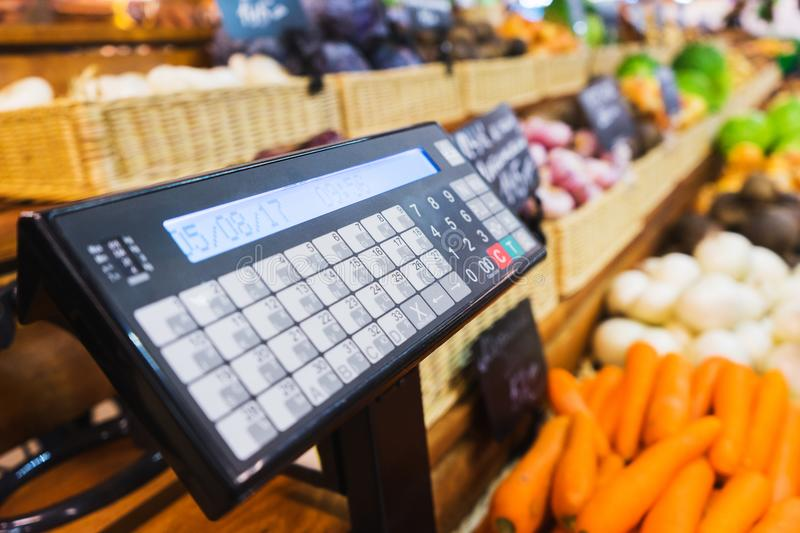 Electronic scales and control panel with a display on the counter of the vegetable market. Farm products and healthy food. Fruits and vegetables, trade. Soft stock photos