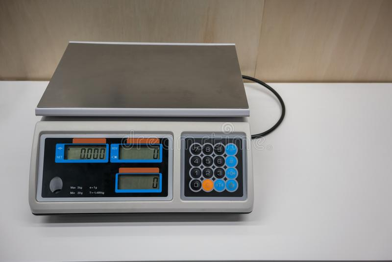 Electronic Scales for weighing food or candy. In front of wooden wall royalty free stock photo