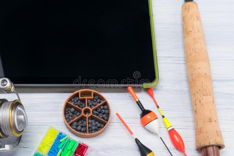 Electronic tablet and equipment for fishing rods on a bright table royalty free stock photography