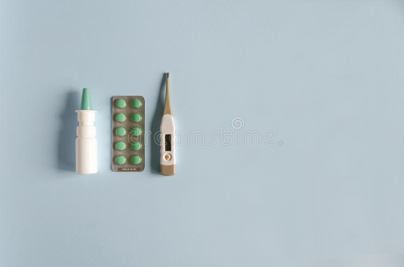 Electronic thermometer, nasal spray, pills for the treatment of illness, flu and cold. flat lay, soft focus, copy space. royalty free stock photo