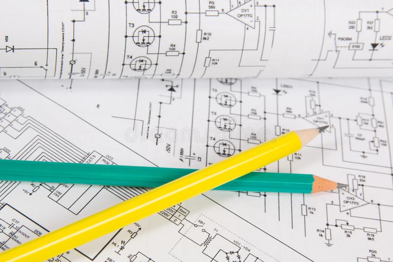 Printed drawings of electrical circuits and pencils. Science, technology and electronics. Electronics and Engineering. Printed drawings of electrical circuits stock images