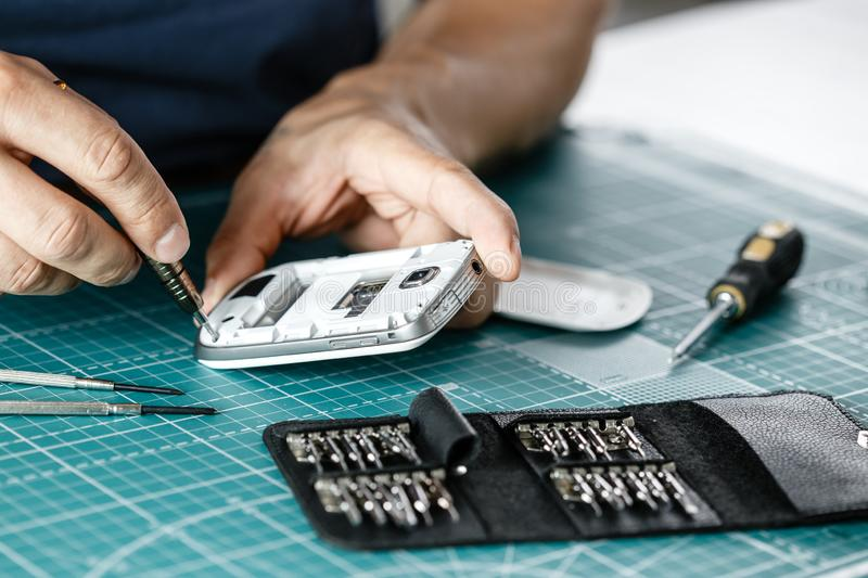 Electronics repair service. Technician disassembling smartphone for inspecting royalty free stock images