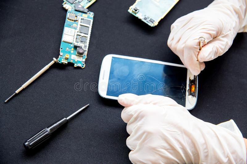 Electronics repair service - technician is fixing broken cell phone. Electronics repair service concept - technician is fixing broken cell phone stock photo