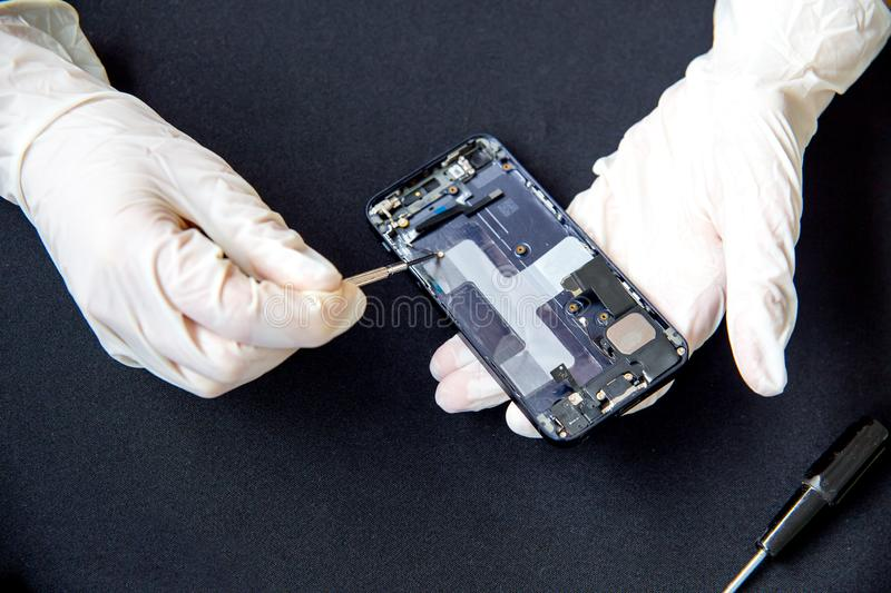 Electronics repair service - technician is fixing broken cell phone. Electronics repair service concept - technician is fixing broken cell phone stock images