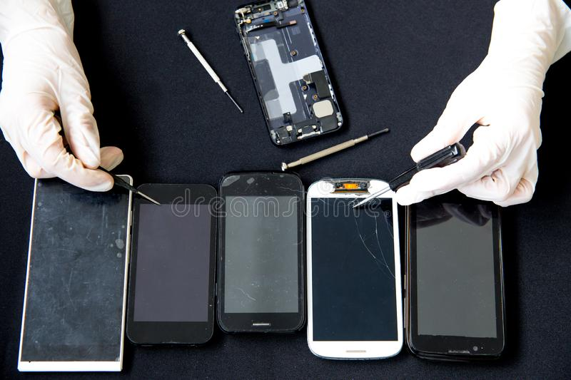 Electronics repair service - technician is fixing broken cell phone. Electronics repair service concept - technician is fixing broken cell phone royalty free stock photography