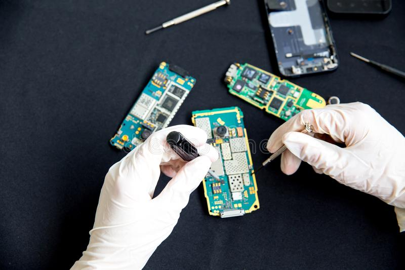 Electronics repair service - technician is fixing broken cell phone. Electronics repair service concept - technician is fixing broken cell phone royalty free stock photos