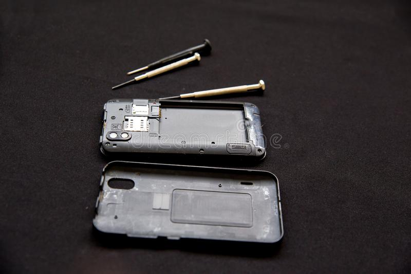 Electronics repair service - technician is fixing broken cell phone stock image