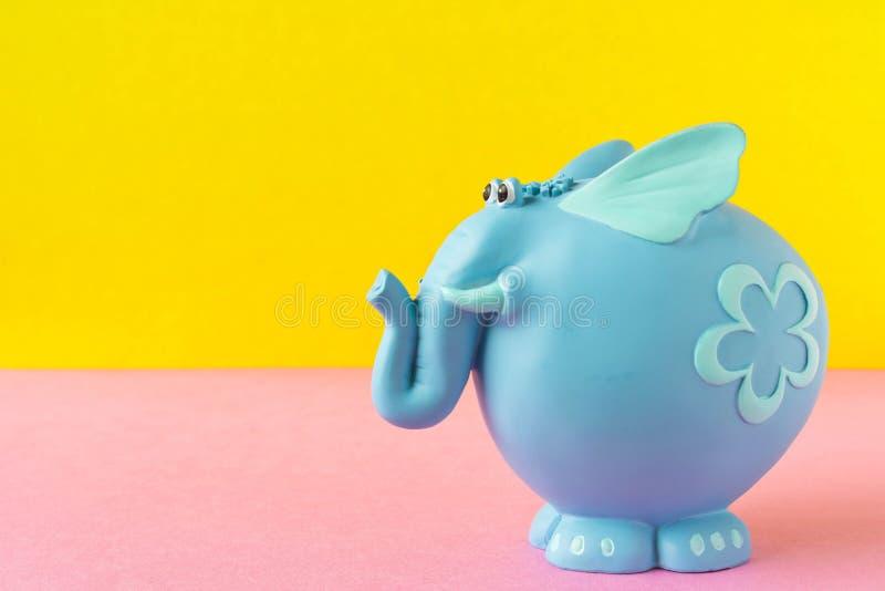 Elefante azul engraçado do brinquedo Em um fundo amarelo-cor-de-rosa imagem de stock royalty free