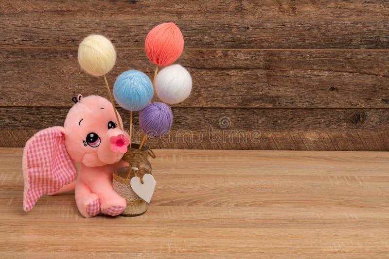 Elefante relleno y bola en colores pastel de las lanas en los palillos imagenes de archivo