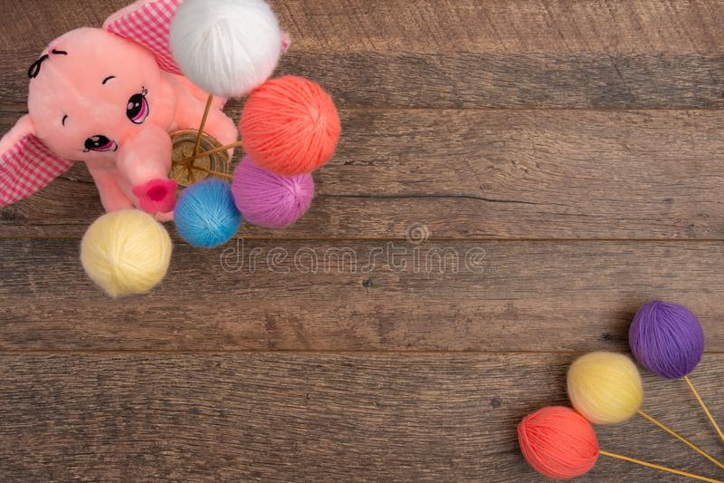 Elefante relleno y bolas en colores pastel de las lanas en los palillos foto de archivo
