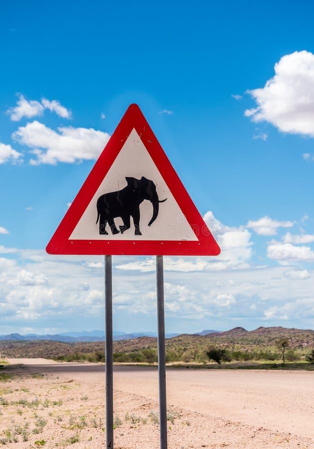 Elefanter som korsar vägvarningstecknet, Damaraland, Namibia arkivfoton