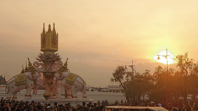 Elefantskulptur under aftonljus över storslagen slott och thailändskt folk royaltyfri fotografi
