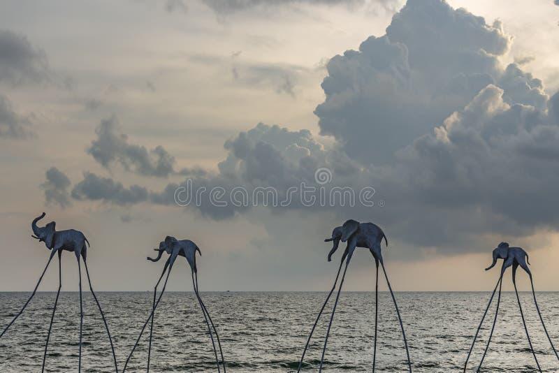 Elefantskulpturer över shorelinen på klubban för solnedgångSenato strand arkivfoton