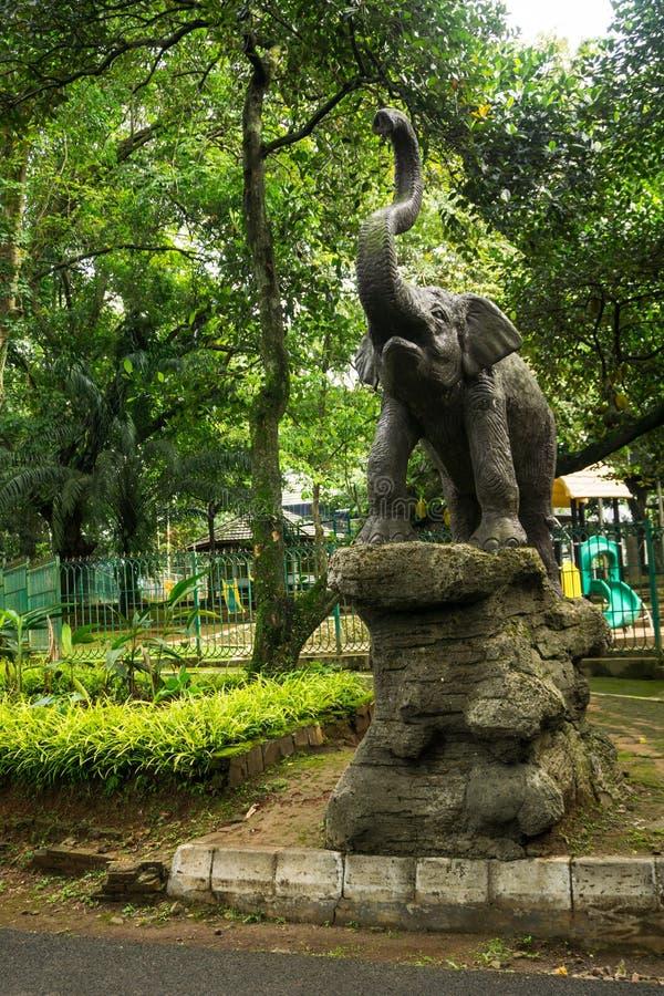 Elefantstatue, die auf Felsen vor Kinderspielplatz Foto eingelassenem Ragunan-Zoo Jakarta Indonesien steht stockfotos